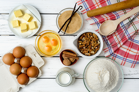 Baking cake in rural kitchen - dough recipe ingredients (eggs, flour, milk, butter, sugar) on white wooden table from above.